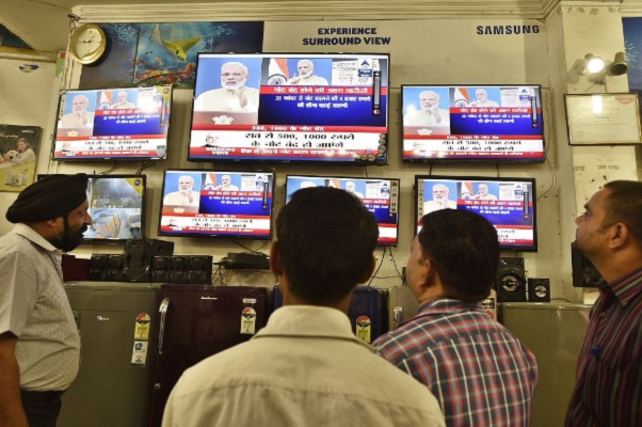 People watching TV during Prime Minister Narendra Modi's address to the nation on 8 November 2016, when he announced the scrapping of Rs 500 and Rs 1,000 notes. (Sanjeev Verma/Hindustan Times via Getty Images)