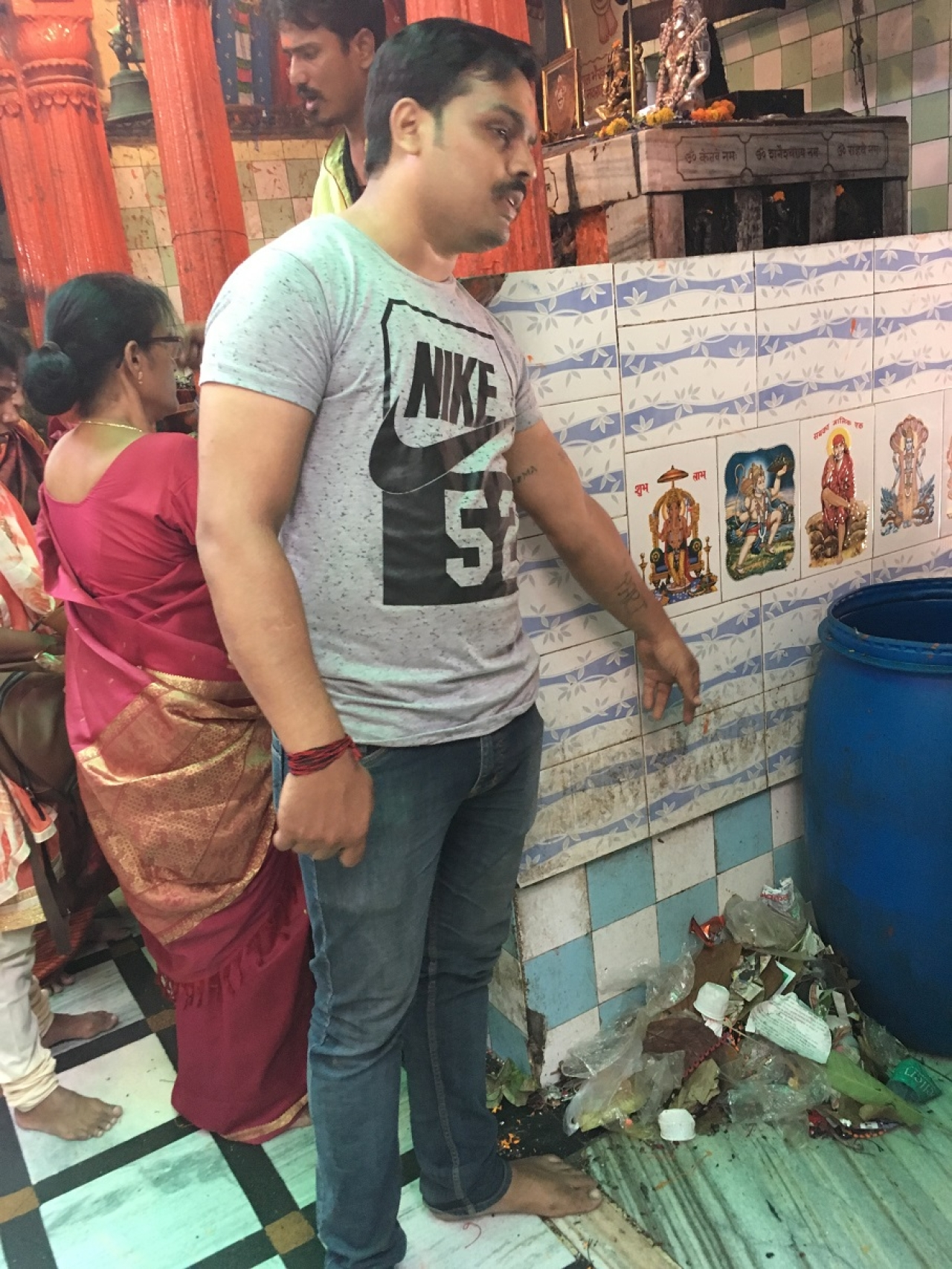 A volunteer at the Kal Bhairav temple points to an unused dustbin.