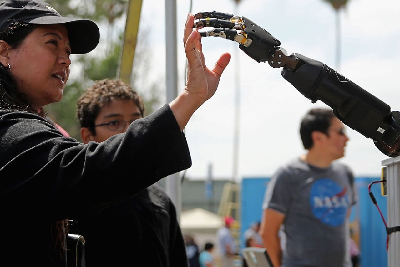 A woman reaches to touch a robotic arm developed by the Johns Hopkins University Applied Physics Laboratory, on display at an expo in California. (Chip Somodevilla/GettyImages)