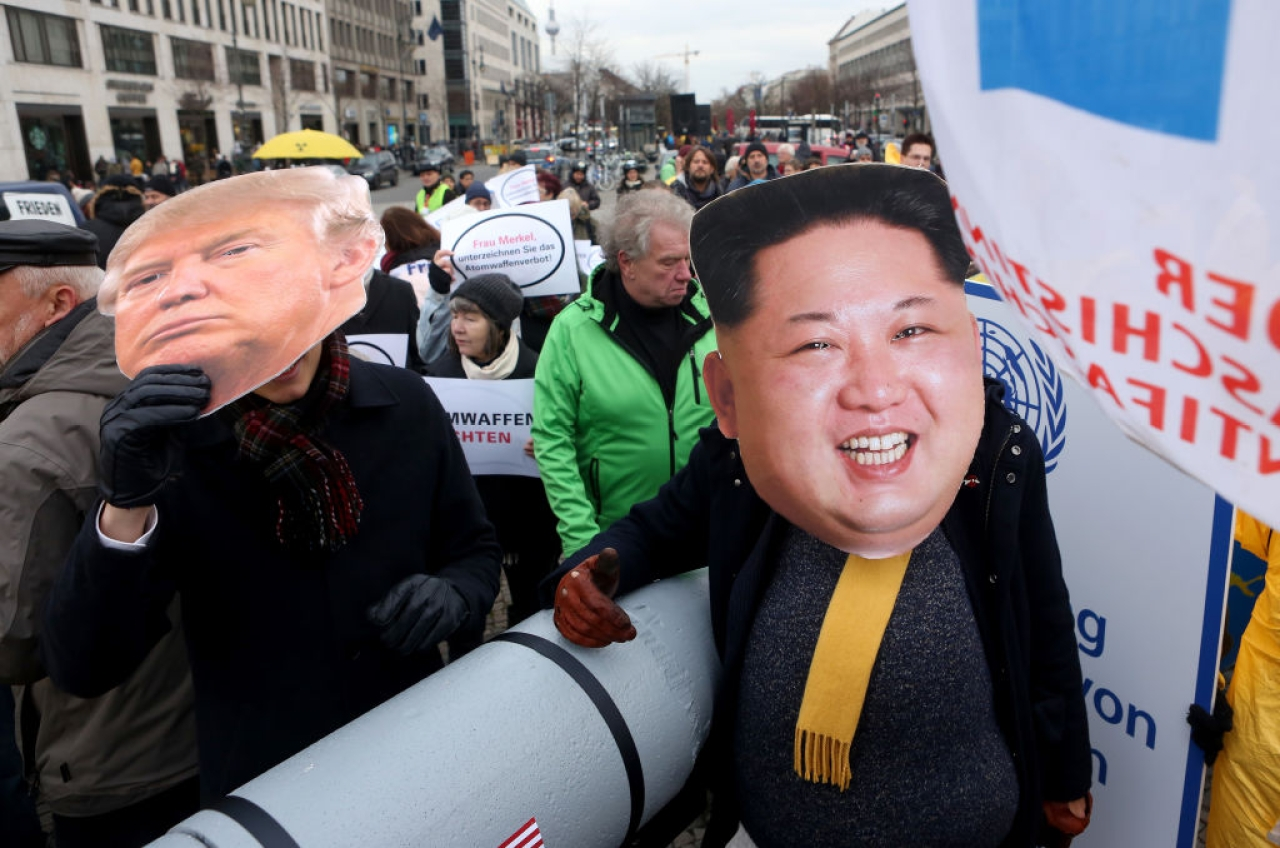 An activist with a mask of Kim Jong-un and another with a mask of Donald Trump march with a model of a nuclear rocket during a demonstration against nuclear weapons in Berlin, Germany.  (Adam Berry/Getty Images)