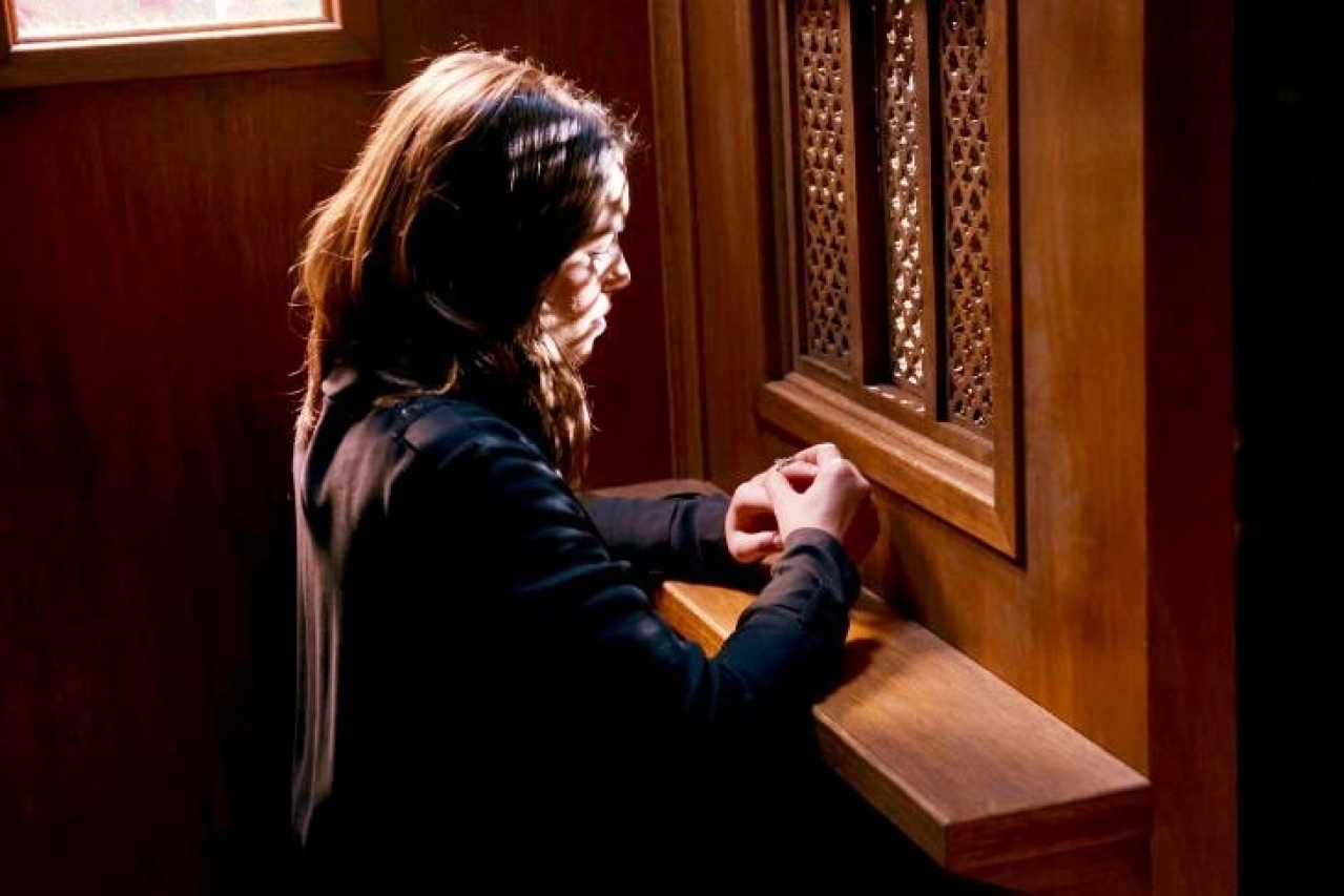 A woman makes a confession before a priest.