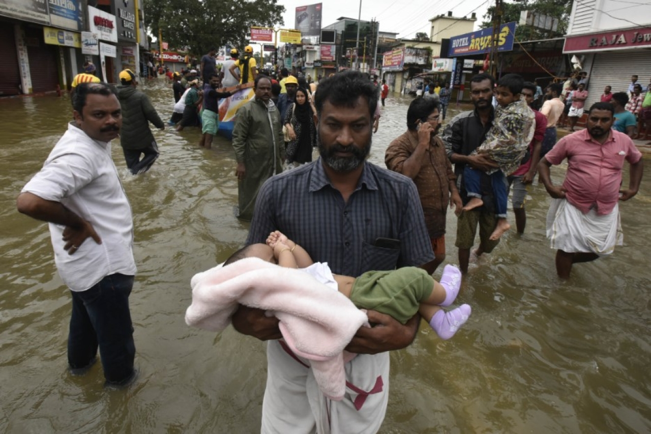 A man carrying a child through the flood water to a safe place at Panadala, on August 18, 2018 in district Pathanamthitta, Kerala. (Raj K Raj/Hindustan Times via Getty Images)