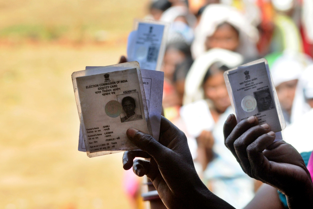 Voters showing voter ID card while standing in queue to cast their vote at a polling booth at a Chhattisgarh village. (Parwaz Khan/Hindustan Times via GettyImages)