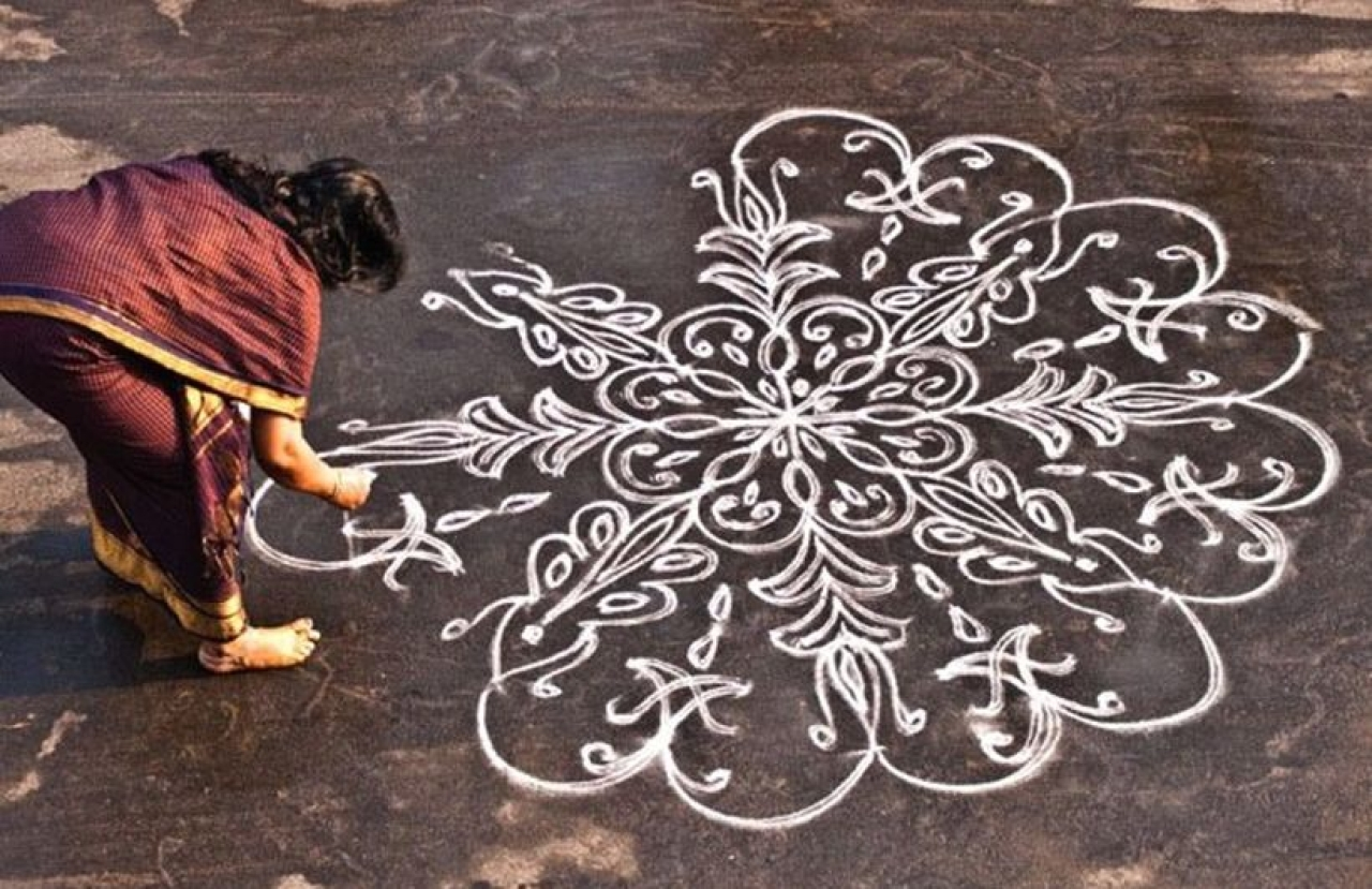 A woman works on a <i>kolam</i> in front of her house.