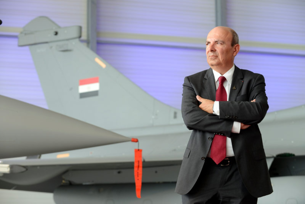 Dassault Aviation CEO Eric Trappier with a Rafale fighter jet in the background.
