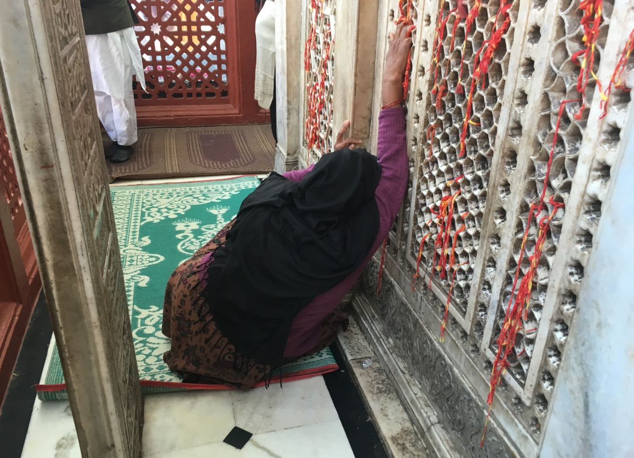 A woman prays from behind the stone-latticed wall on three sides of the main shrine.