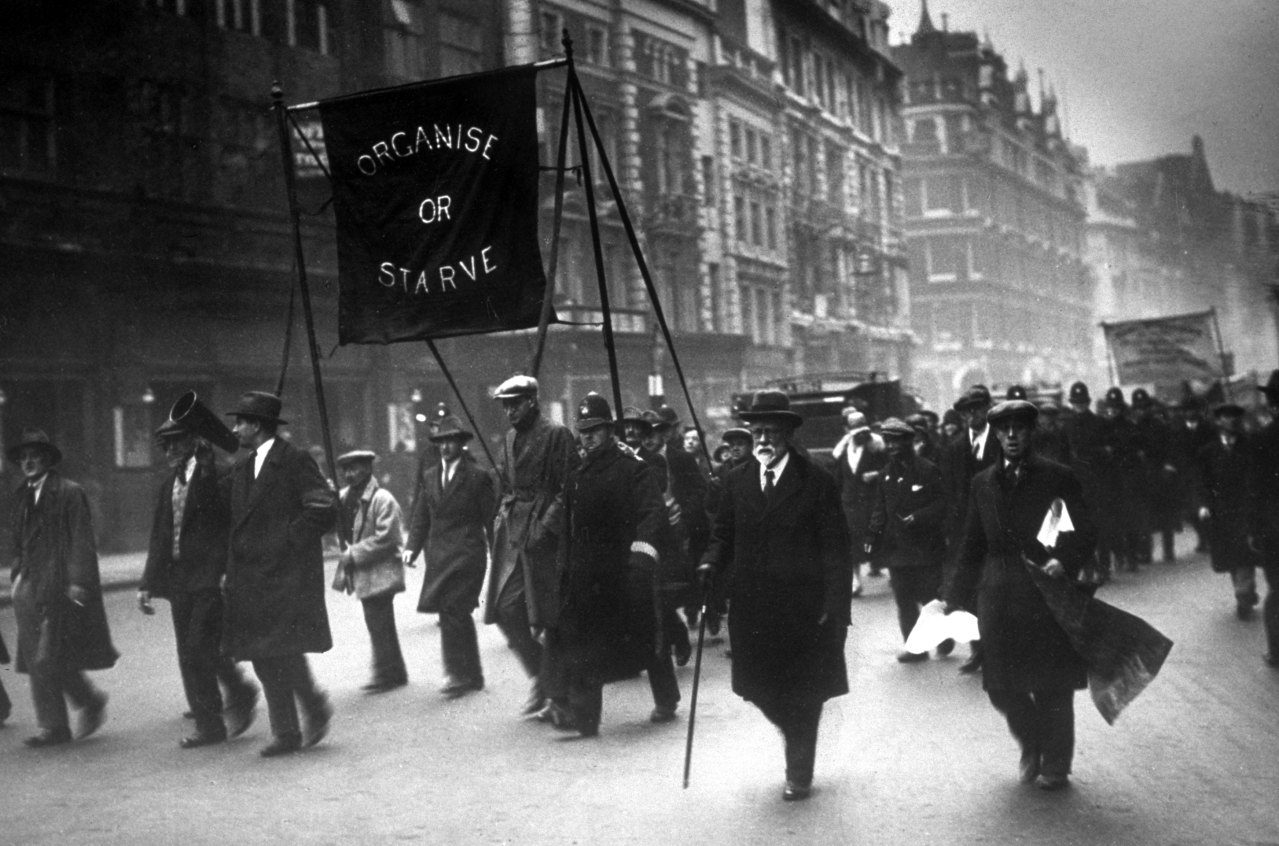 Unemployed men marching along the Thames embankment, carrying a banner reading 'Organise or Starve'. (Topical Press Agency/Getty Images)