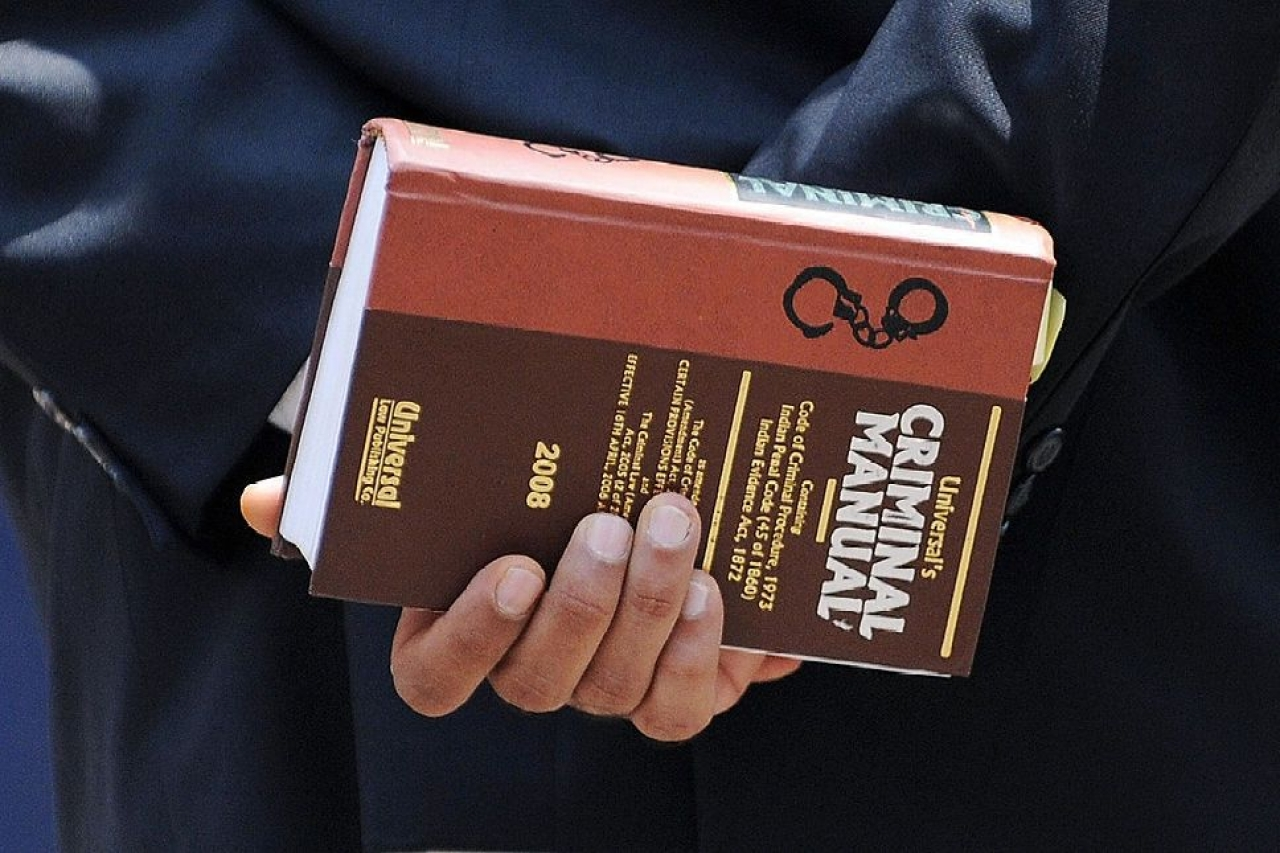 A lawyer holds a criminal manual (INDRANIL MUKHERJEE/AFP/Getty Images).