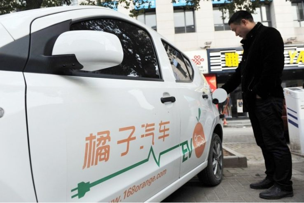 A man charging an electric vehicle at a station in Linan, east China's Zhejiang province. (Stringer/AFP/Getty Images)