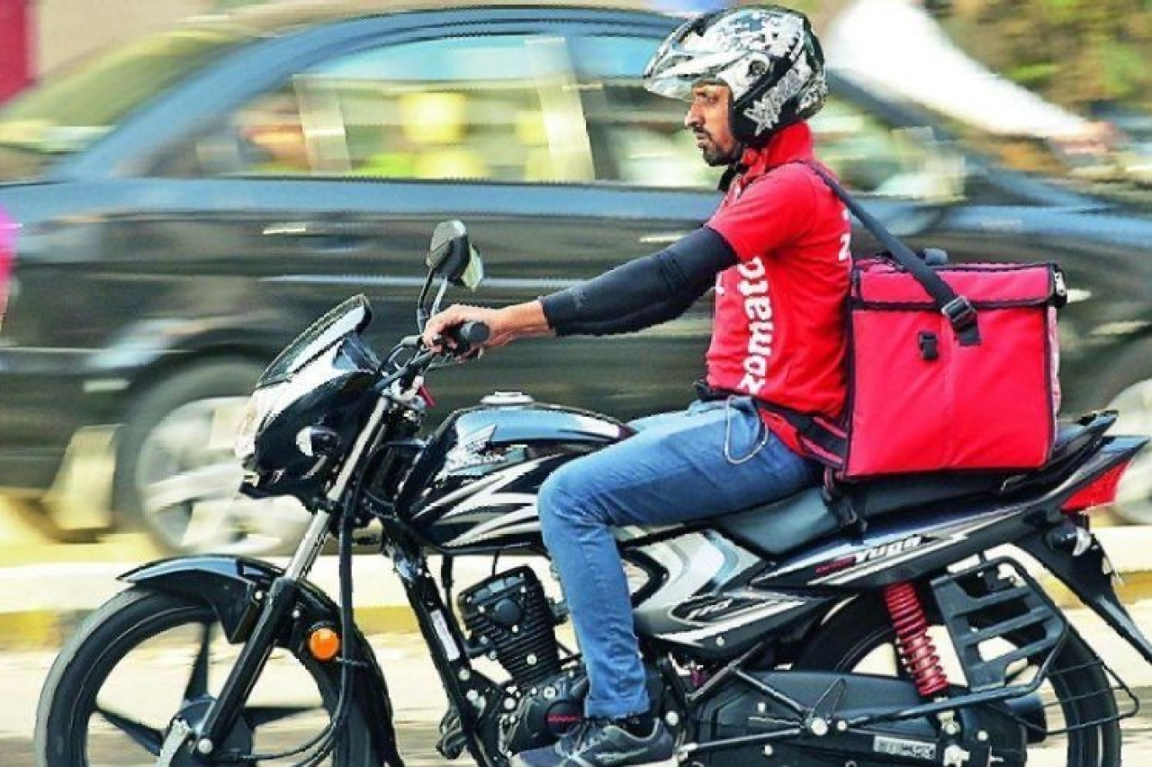 A Zomato delivery boy on a motorcycle.