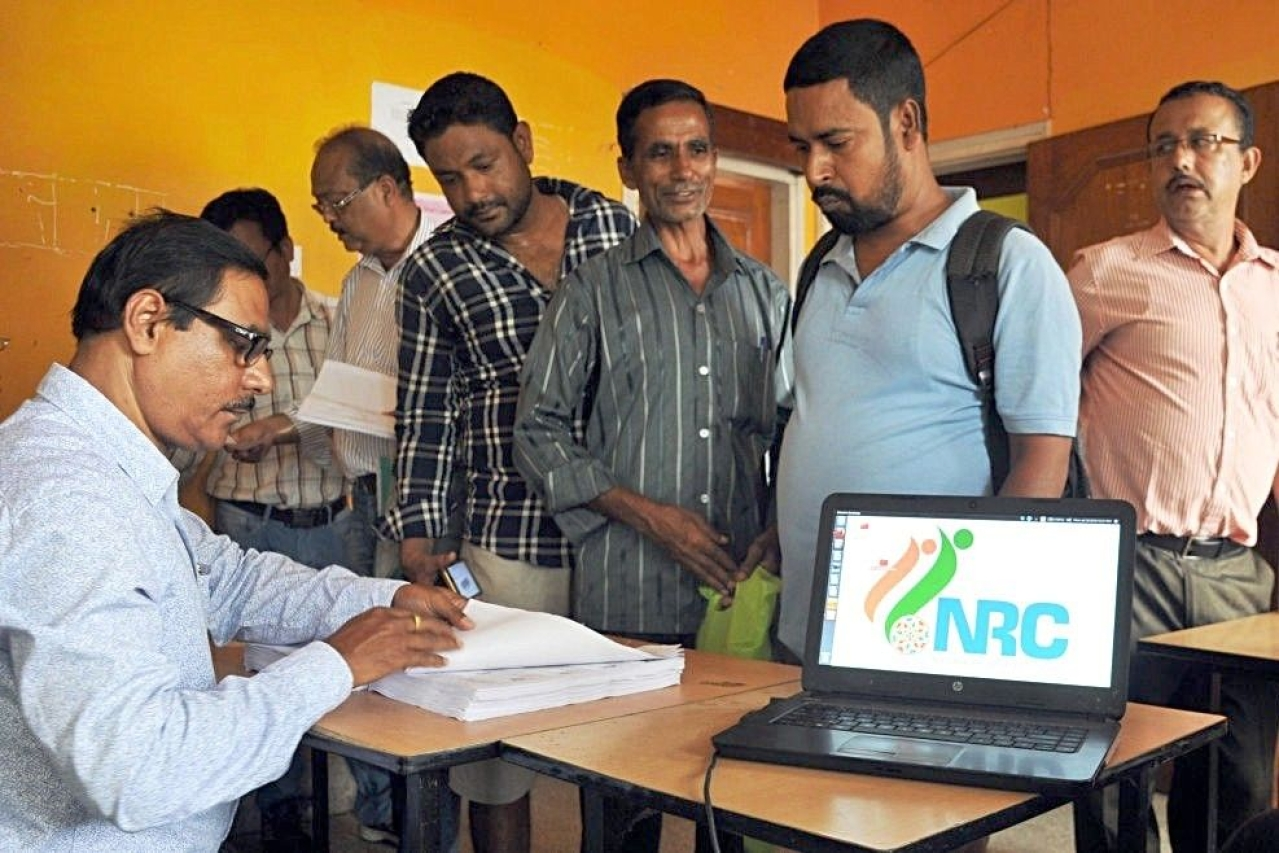 People check their names on the final draft list of Assam's NRC list in Guwahati.  (Rajib Jyoti Sarma/Hindustan Times via GettyImages)