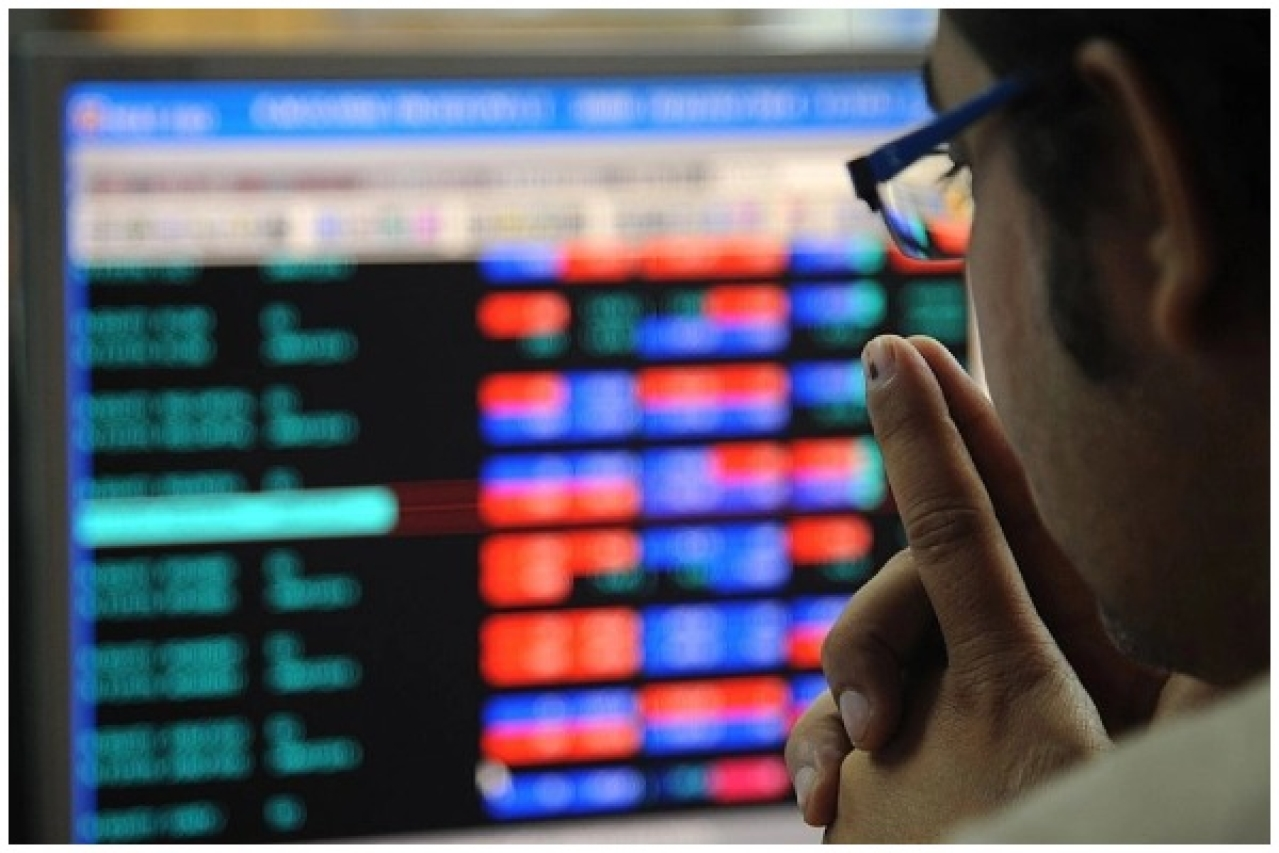 An investor looking at a screen displaying stocks.