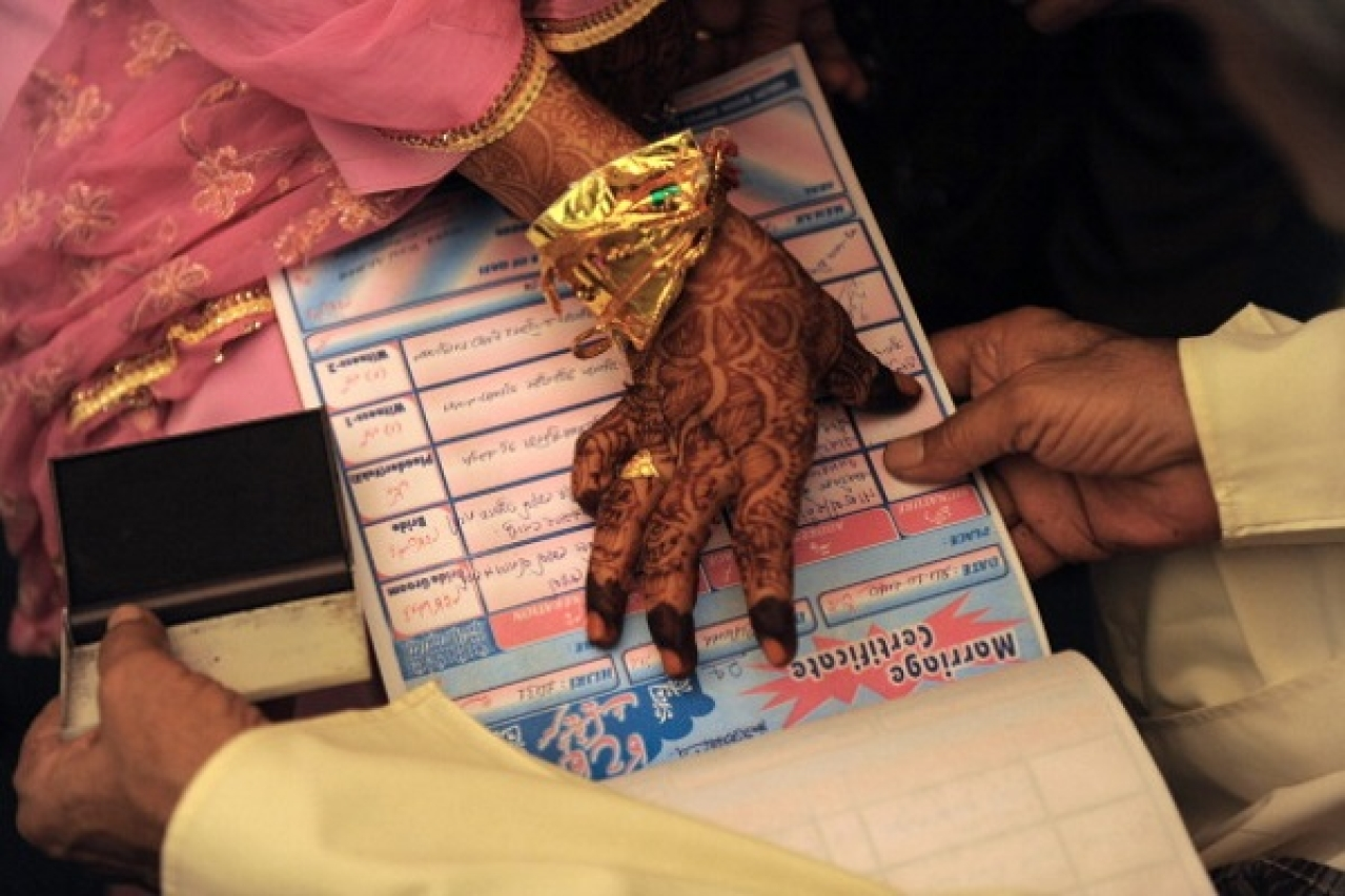 An Indian Muslim bride puts a thumb impression on a marriage certificate in the presence of religious leaders and a relative (representative image) (SAM PANTHAKY/AFP/GettyImages)