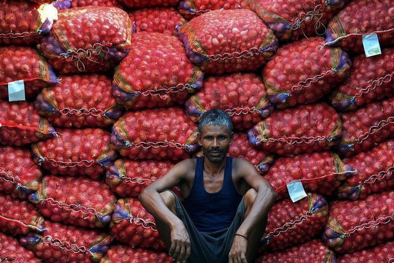 A labourer takes a break from unloading sacks of onions from a truck. (Representative Image )(Sanjay Kanojia/AFP/Getty Images)