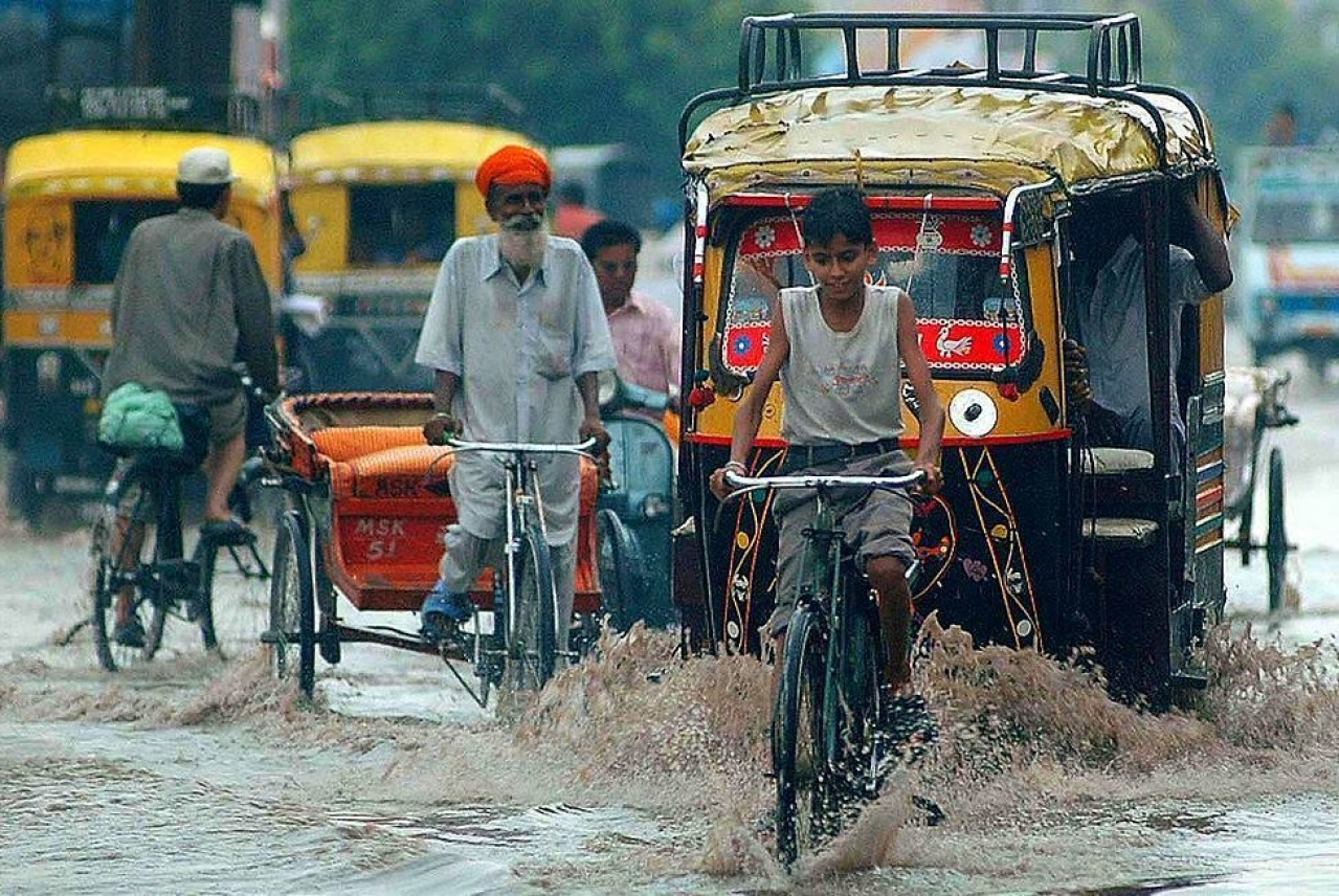 Indian commuters make their way along a waterlogged street during a heavy downpour of monsoon rain in Amritsar. (NARINDER NANU/AFP/Getty Images)