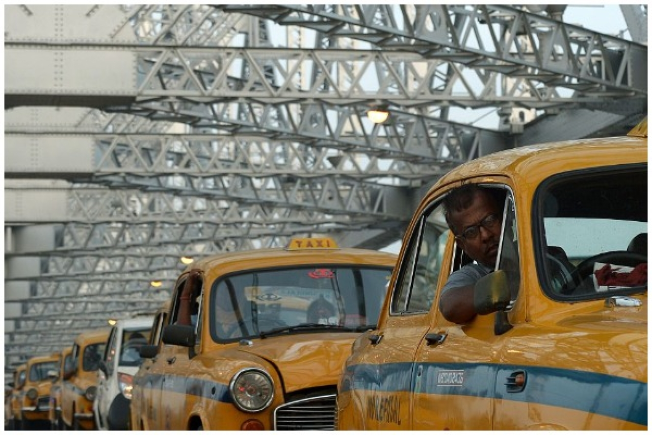 Kolkata taxi drivers in their out-dated cars on Howrah Bridge in Kolkata (DIBYANGSHU SARKAR/AFP/Getty Images)