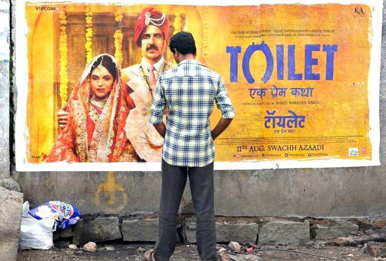 An Indian man urinates on a wall on the roadside in front of a poster for the Hindi film 'Toilet: Ek Prem Katha', which is inspired by the true-life tale of one man's battle to build toilets in his village in rural India. / AFP PHOTO / NOAH SEELAM (Photo: NOAH SEELAM/AFP/Getty Images)