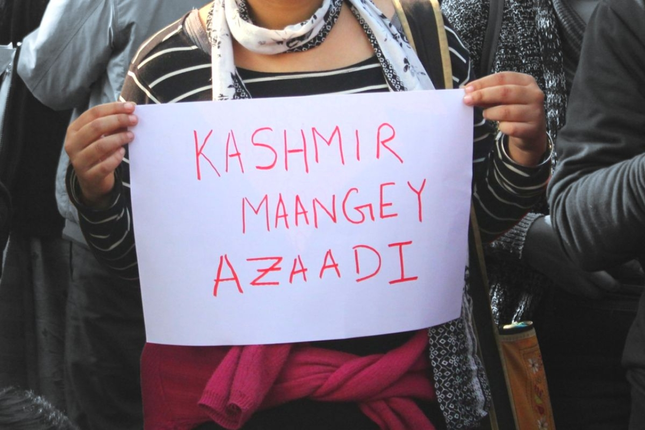 An anti-CAA protester holding a 'Kashmir Maangey Azaadi' poster.