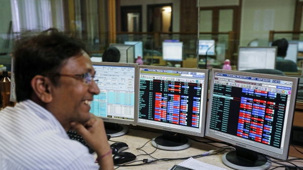 A broker laughs while speaking to a colleague, as they trade on their computer terminals at a stock brokerage firm in Mumbai, 4 March  2015.