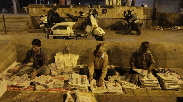 Newspaper hawkers prepare for the morning delivery. (Photo: AP)