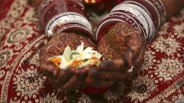 A bride holds flowers with her hands decorated with henna paste during her wedding ceremony
