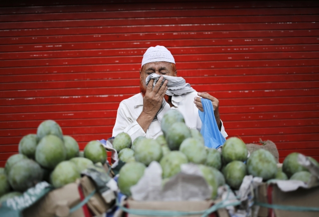<!--StartFragment-->A vendor sneezes while selling mangoes along a roadside in the old quarters of Delhi. (Photo: Reuters)<!--EndFragment-->
