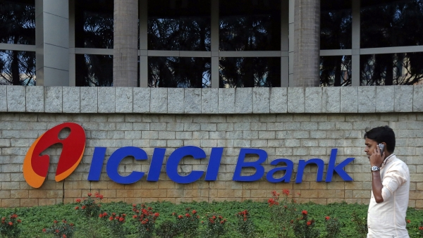 A pedestrian walks past a logo of ICICI Bank at its headquarters in Mumbai.