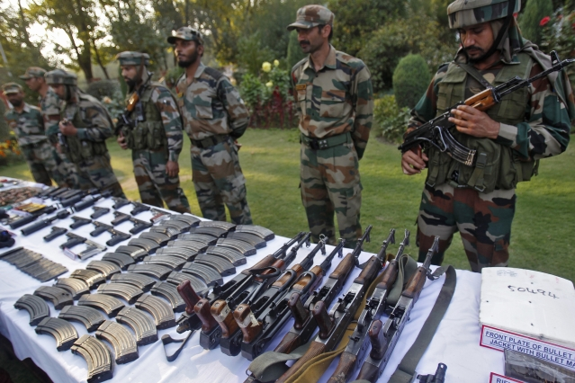 Indian Army soldiers stand behind a display of seized arms and ammunition at a garrison in Srinagar, October, 2013.  (Photo: Reuters)