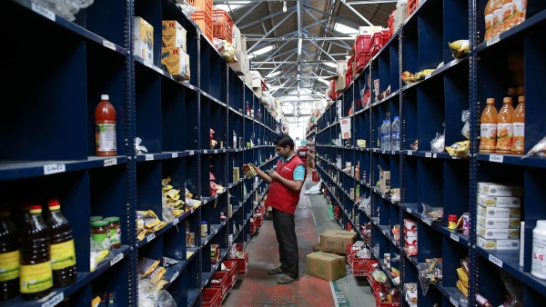 An employee scans a package for an order at a warehouse on the outskirts of Mumbai. (Photo: Reuters)