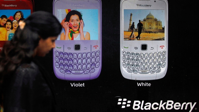 A woman walks past a Blackberry advertisement billboard in Mumbai.