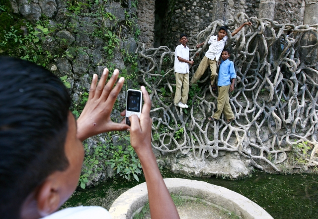 Children pose hanging onto the cement roots at Nek Chand's Rock Garden (Photo: Reuters)