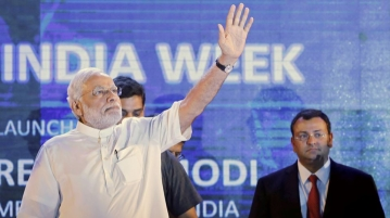 "Prime Minister Narendra Modi waves as Cyrus Mistry (R), chairman of Tata Group watches during the launch of ""Digital India Week"" in New Delhi, India, July 1, 2015. (Photo: Reuters)"