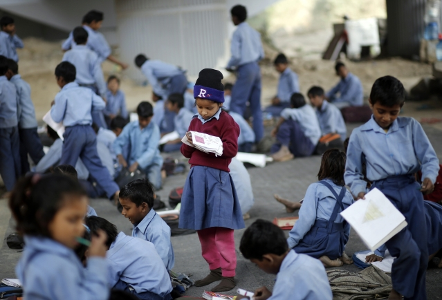 A schoolgirl reads from a textbook at an open-air school in New Delhi, November, 2014. (Photo: Reuters)