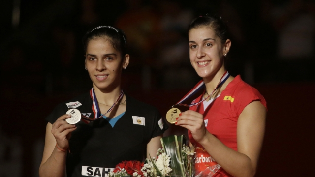 Spain's Carolina Marin, right, and India's Saina Nehwal pose with their medals after the women's singles final at the Badminton World Championships.