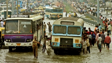 People push a bus through a flooded road in Bengaluru, October 24, 2005. (Photo: Reuters)