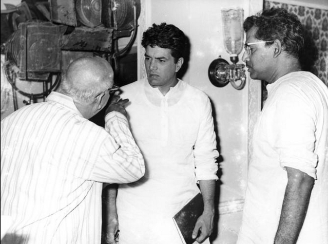A photo from Mukherjee's <i>Satyakam</i> shoot. Actor David Abraham (L) talks to Dharmendra(centre) as Mukherjee (R) looks on (Photo: Twitter/@jaiarjun)