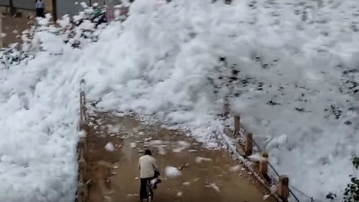 Toxic foam-shower from Bengaluru's lake, flying over people on the road (Photo courtesy: The News Minute)