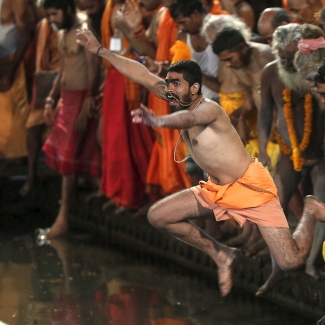 Sadhus jump in a holy pond during the first <i>Shahi Snan</i> (grand bath) at the <i>Kumbh Mela</i> in Trimbakeshwar.