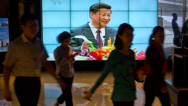 People walk past a large videoscreen showing Chinese President Xi Jinping during his trip to the United States from Chinese state broadcaster CCTV in an office building in Beijing, Friday, Sept. 25, 2015. (Photo: AP)