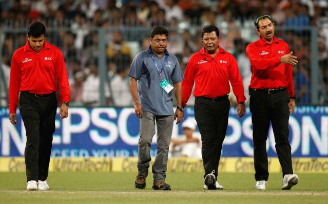 Umpires Anil Chaudhary, right, Vineet Kulkarni, left, and Chettithody Shamshuddin, second right, inspect the wet ground in Kolkata. (Photo: AP)