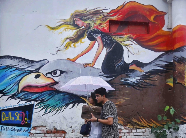 A couple walk in front of a graffiti painted wall during a rain shower in Delhi (Photo: Reuters) (Picture for representation purposes only)