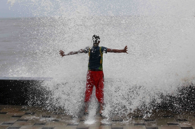 A boy stands near a wall as a wave comes crashing in Mumbai (Photo: Reuters) (Picture for representation purposes only)