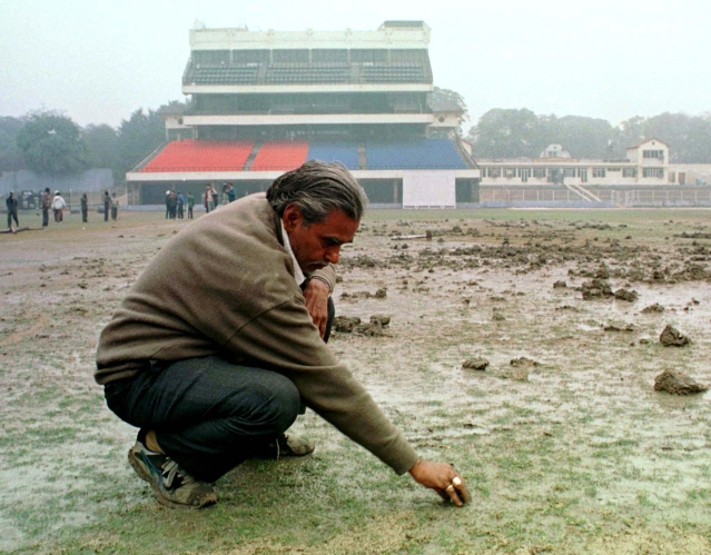 Radhe Shyan Sharma, curator of the pitch at Delhi's Feroz Shah Kotla cricket stadium, assesses the damaged pitch in New Delhi on January 7, 1999, after Shiv Sena activists dug up the pitch three weeks ahead of a Test match between India and Pakistan. (Photo: Reuters)