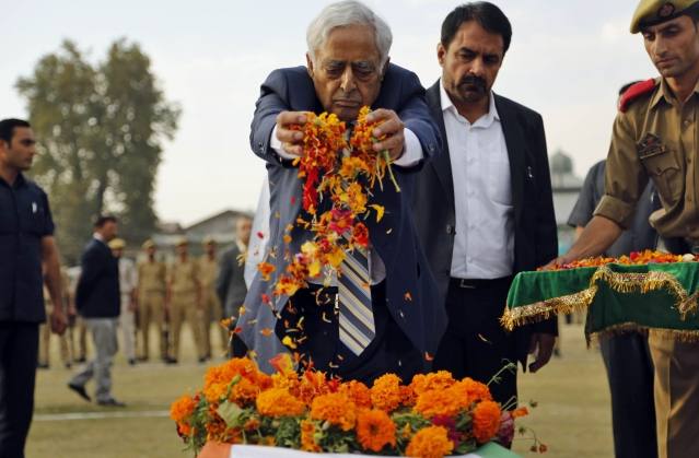 Chief Minister of Jammu and Kashmir, Mufti Mohammad Sayeed, offers flower petals on the coffin of Indian police officer Altaf Ahmed during a wreath laying ceremony in Srinagar. (Photo: AP)