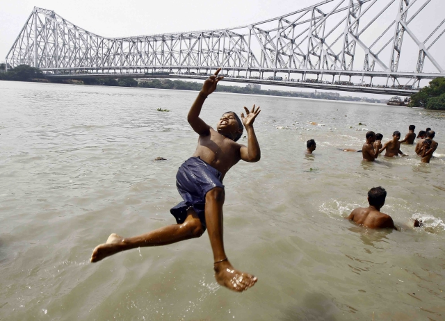 A boy jumps into the Ganges river to cool off himself on a hot summer day in Kolkata (Photo: Reuters) (Picture for representation purposes only)
