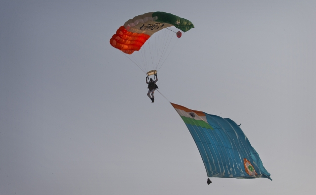 A member of an Indian Air Force (IAF) Akash Ganga skydiving team dives with an IAF flag during the Air Force Day parade at Hindon Air Force base near New Delhi. (Photo: AP)