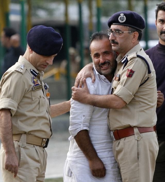 A police officer comforts a relative of Altaf Ahmed during his wreath-laying ceremony in Srinagar. (Photo: AP)