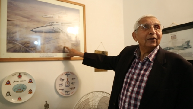Keelor pointing towards an artist's rendition of his famous dogfight with the Pakistani Air Force Sabre jets. (Photo: <b>The Quint</b>)