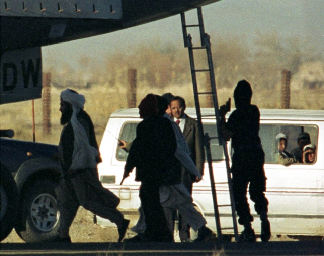 Masked hijackers and Taliban leaders guard IC-814 at the Kandahar airport, Afghanistan.