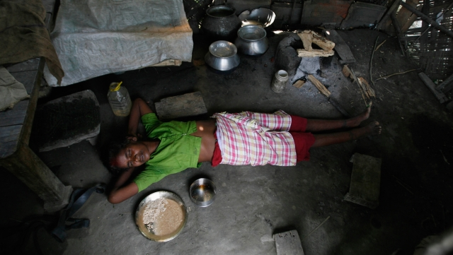 A tea garden worker suffering from malnutrition lies inside her damaged house in the closed Bharno Bari tea garden estate, about 115 km  from Siliguri, West Bengal. (File photo: Reuters)